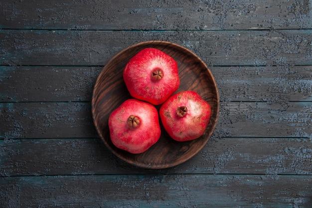 Bovenaanzicht van verre kom granaatappels kom rijpe rode granaatappels op tafel
