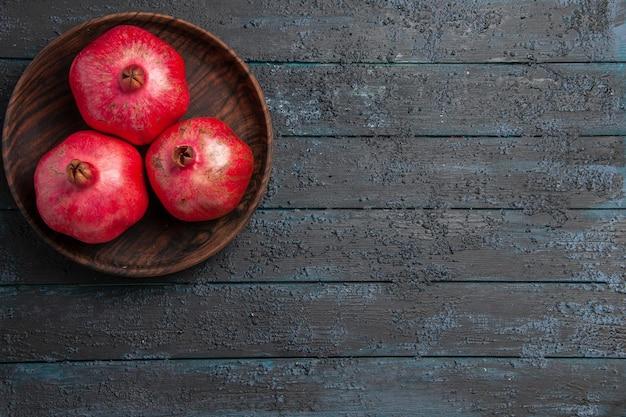 Bovenaanzicht van verre kom met granaatappels kom met rijpe rode granaatappels aan de linkerkant van tafel