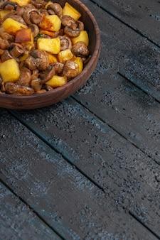 Bovenaanzicht van verre kom met voedselaardappelen en paddenstoelen in de houten kom links bovenaan de tafel