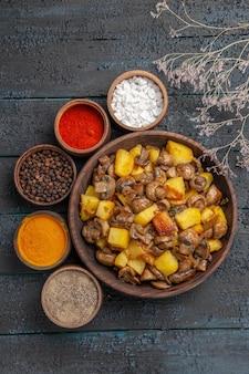 Bovenaanzicht van verre kom met voerbak met champignons en aardappelen, verschillende kruiden eromheen naast de boomtakken