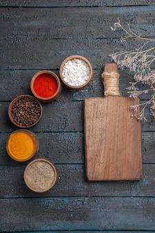 Bovenaanzicht van verre kruiden en snijplank tussen verschillende kleurrijke kruiden en takken op tafel