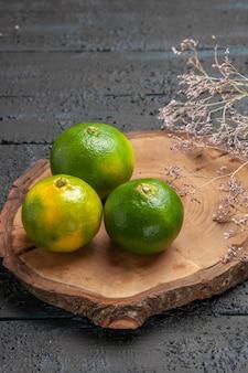 Bovenaanzicht van verre limoen aan boord van limoenen op bruin bord op de grijze tafel naast takken