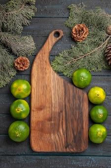 Bovenaanzicht van verre limoenen en bord groengele limoenen naast de snijplank boomtakken en kegels