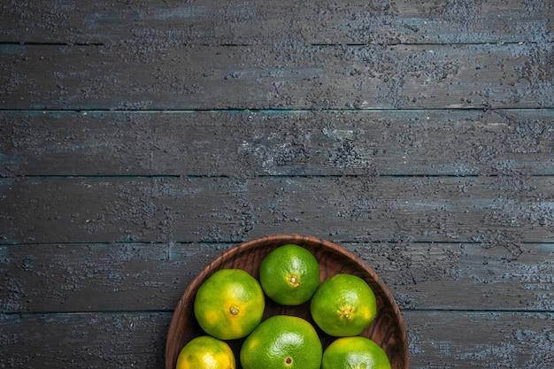 Bovenaanzicht van verre limoenen in kom groene limoenen in bruine plaat op donkere ondergrond