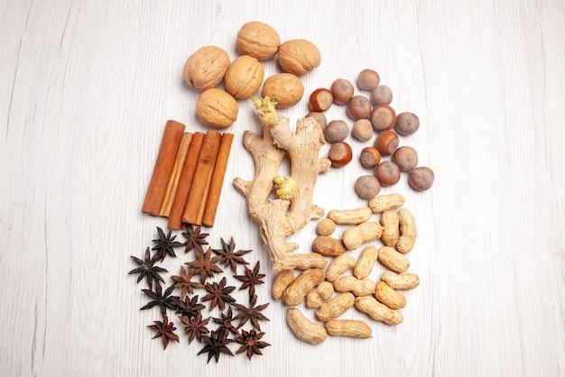 Bovenaanzicht van verre noten hazelnoten walnoten steranijs pinda's en kaneelstokjes op het witte oppervlak
