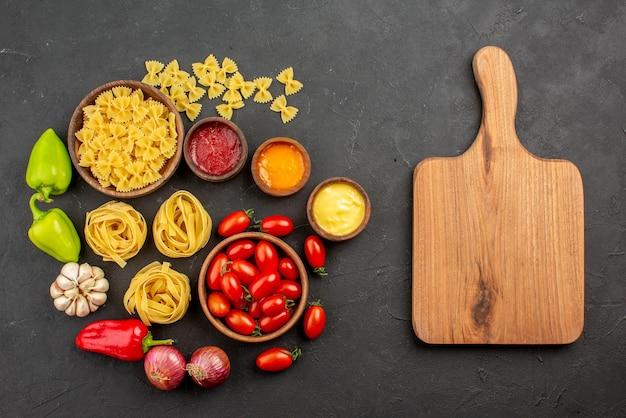 Bovenaanzicht van verre pasta en sauzen tomaten en pasta in kommen paprika knoflook drie soorten sauzen ui naast de snijplank op tafel
