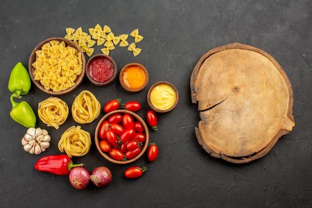 Bovenaanzicht van verre pasta en sauzen tomaten en pasta in kommen paprika knoflook drie soorten sauzen ui naast het houten keukenbord op tafel