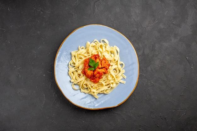 Bovenaanzicht van verre pasta pasta met vlees en jus op de blauwe plaat op de donkere achtergrond