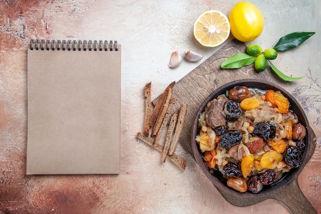 Bovenaanzicht van verre pilaf citroen knoflook het houten bord met pilaf crème notebook