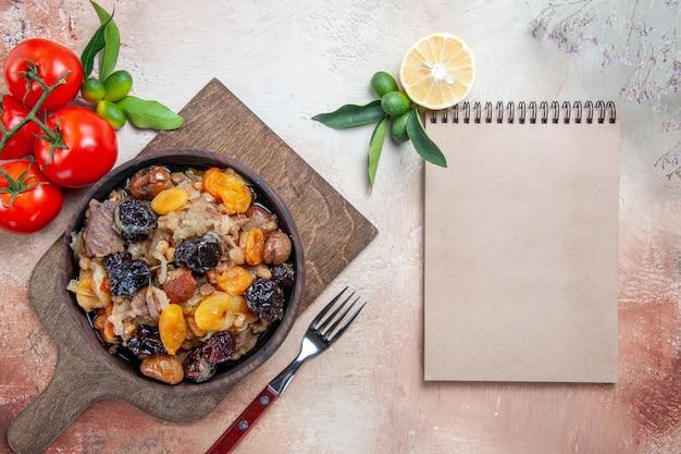 Bovenaanzicht van verre pilaf de snijplank met pilaf vork tomaten citroen crème notebook