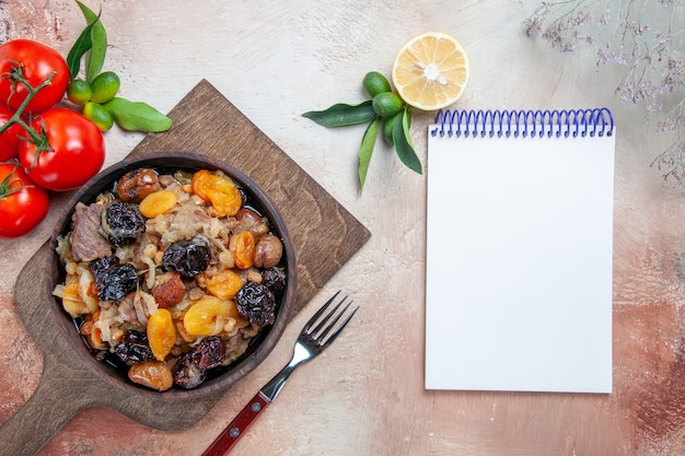 Bovenaanzicht van verre pilaf de snijplank met pilaf vork tomaten citroen witte notebook
