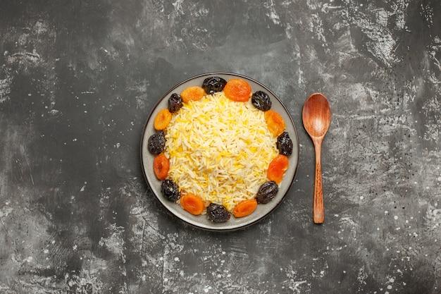 Bovenaanzicht van verre rijst de smakelijke gedroogde vruchten en rijst in de plaatlepel op tafel
