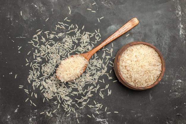 Bovenaanzicht van verre rijst rijst in de lepel en kom op de donkere tafel