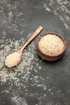 Bovenaanzicht van verre rijstlepel en kom rijst op de donkere tafel