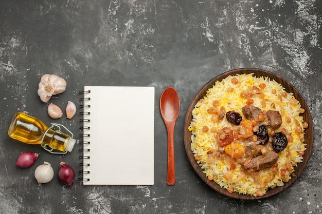 Bovenaanzicht van verre rijstpilaf met vlees ui knoflook fles olie lepel notebook