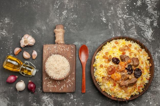 Bovenaanzicht van verre rijstpilaf ui knoflook fles olie lepel kom rijst op het bord