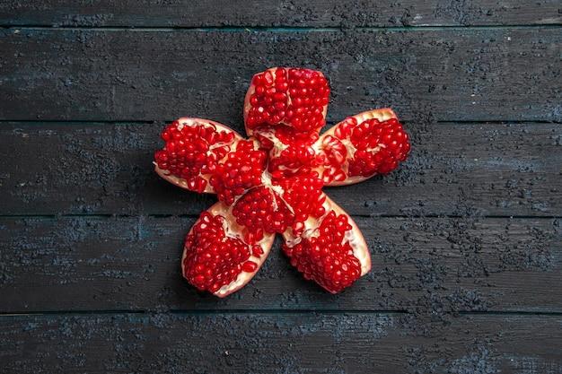 Bovenaanzicht van verre rode granaatappel, smakelijke rode gepilde granaatappel in het midden van grijze tafel