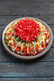 Bovenaanzicht van verre salade met granaatappel kerstsalade met granaatappel en saus in het bord op tafel