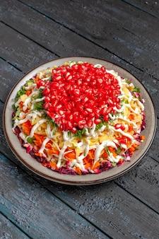 Bovenaanzicht van verre salade met granaatappel kerstsalade met mayonaisezaden van granaatappel en bieten in de plaat op de houten tafel