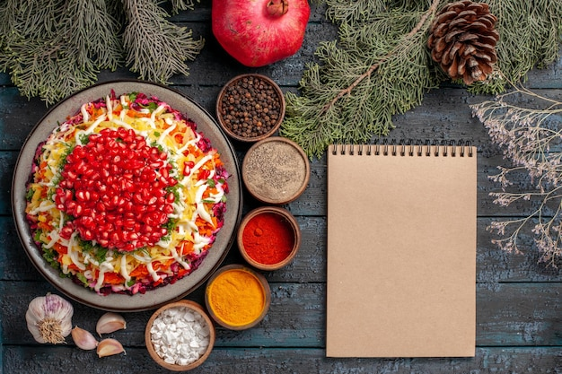 Bovenaanzicht van verre schotel en boomtakken schotel van zaden van granaatappels naast de kommen van kruiden granaatappel crème notebook en boomtakken kegels op de grijze tafel