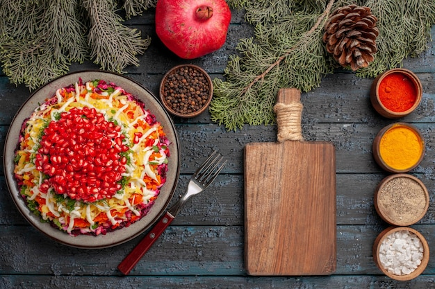 Bovenaanzicht van verre schotel en boomtakken schotel van zaden van granaatappels naast de snijplank kommen met kruiden granaatappelvork en boomtakken kegels