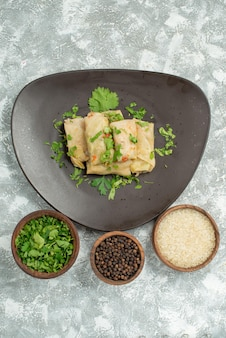 Bovenaanzicht van verre schotel met kruidenbord van gevulde kool en kommen zwarte papperrijst en kruiden in het midden van de tafel