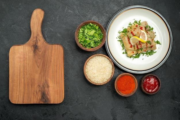 Bovenaanzicht van verre schotel met saus gevulde kool met citroenkruiden en saus op witte plaat en specerijen rijstkruiden en saus in kommen naast houten keukenbord op donkere tafel