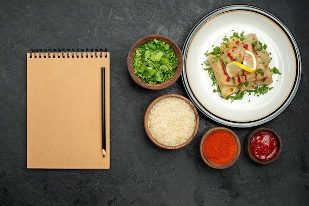Bovenaanzicht van verre schotel met saus gevulde kool met citroenkruiden en saus op witte plaat en specerijen rijstkruiden en saus in kommen naast roomnotitieboekje en potlood op donkere tafel