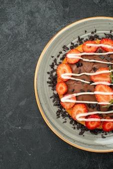 Bovenaanzicht van verre smakelijke desserttaart met aardbei en chocolade op witte plaat aan de linkerkant van donkere tafel