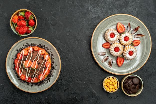 Bovenaanzicht van verre snoep en cake smakelijke cake en koekjes met aardbei en chocolade en kommen met hazelnoten, chocolade en aardbei op zwarte tafel