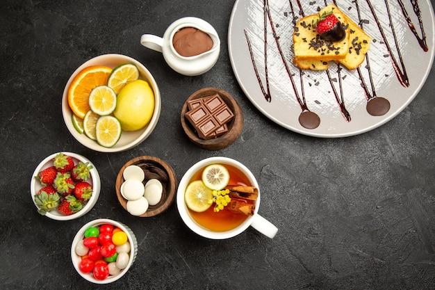 Bovenaanzicht van verre snoepjes grijze plaat van cake naast de kommen van citrusvruchten chocolade snoepjes aardbeien chocolade crème het kopje thee