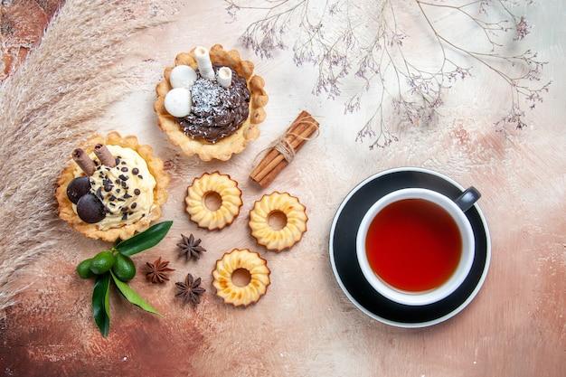 Bovenaanzicht van verre snoepjes kaneel cupcakes koekjes citrusvruchten steranijs een kopje thee