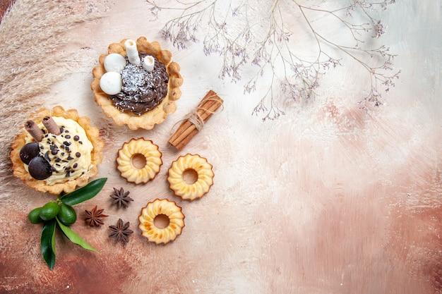 Bovenaanzicht van verre snoepjes kaneel cupcakes koekjes citrusvruchten steranijs