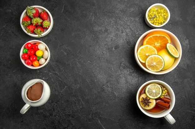 Bovenaanzicht van verre snoepjes met thee een kopje thee met citroen en steranijs en de kommen met kruiden citrusvruchten chocolade crème aardbeien op tafel