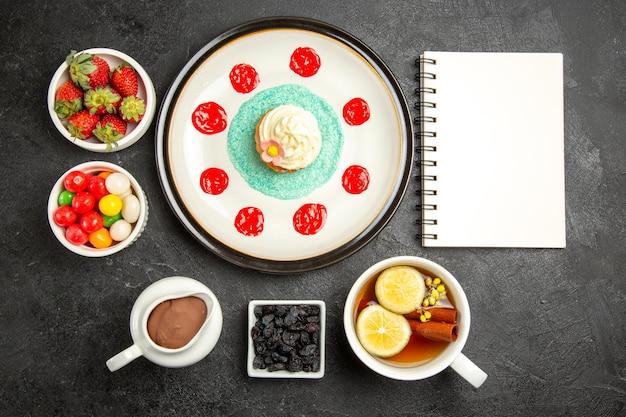 Bovenaanzicht van verre snoepjes met thee witte notitieboekje cupcake met room een kopje kruidenthee met citroen naast de kommen chocoladeroom aardbeien en snoepjes