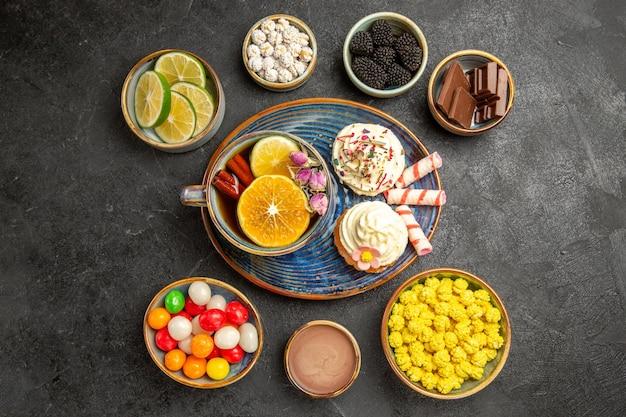Bovenaanzicht van verre snoepjes op de tafel kommen van verschillende bessen chocolade citrusvruchten kleurrijke snoepjes en smakelijke cupcakes en een kopje thee met citroen en kaneelstokjes op de donkere tafel