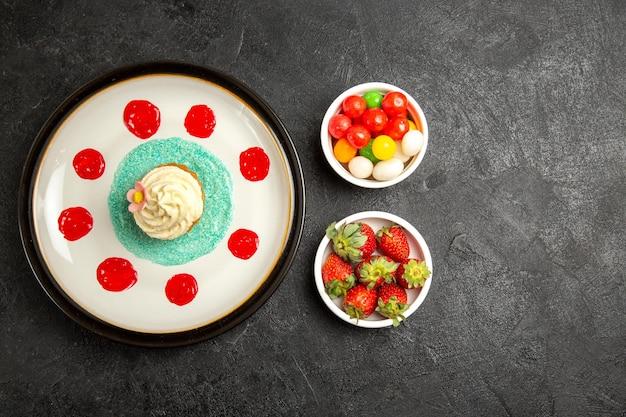 Bovenaanzicht van verre snoepjes op de tafel witte cupcake en kommen met snoep en aardbeien op de zwarte tafel