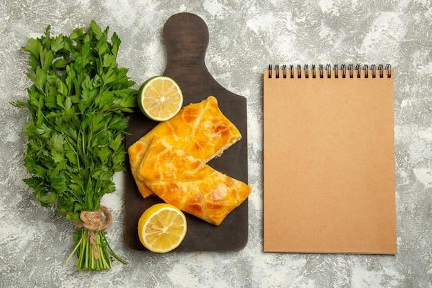 Bovenaanzicht van verre taarten, kruiden, kaastaarten en citroen op het houten bord naast het crèmekleurige notitieboekje op tafel
