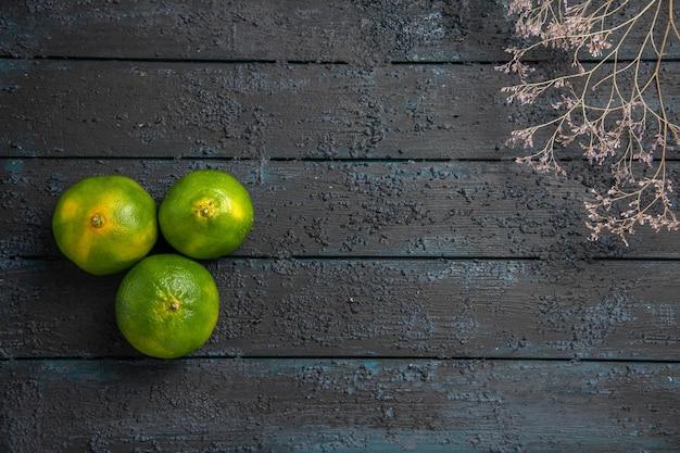 Bovenaanzicht van verre takken en limoenen drie limoenen op tafel met boomtakken