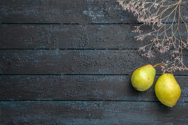Bovenaanzicht van verre takken en peren twee rijpe peren naast boomtakken aan de rechterkant van de tafel