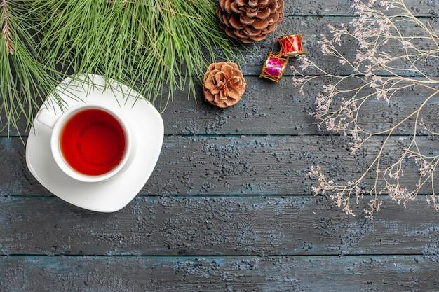Bovenaanzicht van verre thee kerstspeelgoed sparrenboom met kegels en een kopje thee op de schotel