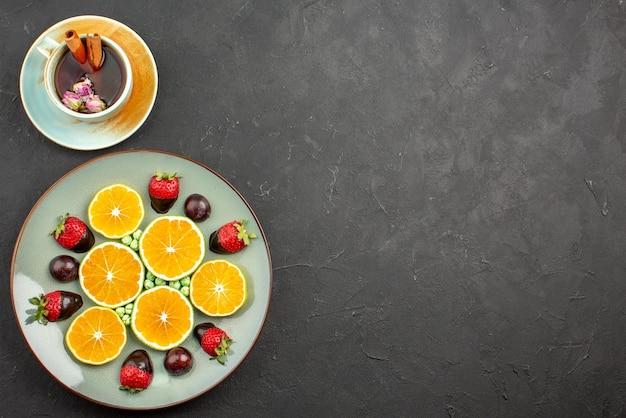 Bovenaanzicht van verre thee met fruit met chocolade bedekte aardbei, smakelijke gehakte sinaasappel en groene snoepjes naast een kopje thee met kaneelstokjes aan de linkerkant van de donkere tafel