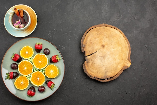 Bovenaanzicht van verre thee met fruit met chocolade bedekte aardbei, smakelijke gehakte sinaasappel en groene snoepjes naast een kopje thee met kaneelstokjes naast snijplank