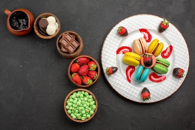 Bovenaanzicht van verre zoete schotel met macaroon en aardbeien naast de kommen met chocoladesuikergoed en aardbeien op tafel