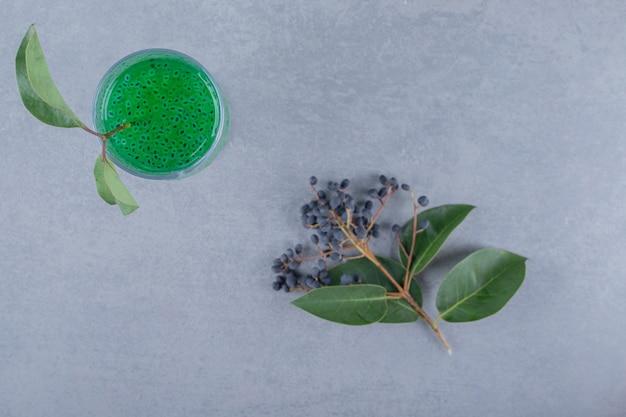 Bovenaanzicht van vers appelsap in groene bladeren over grijs oppervlak