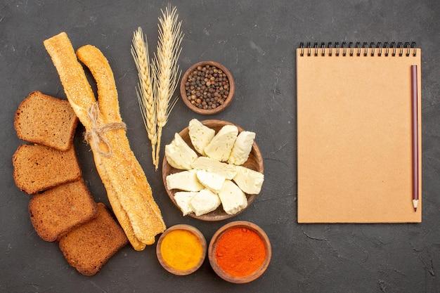 Bovenaanzicht van vers brood met witte kaas en kruiden op donker