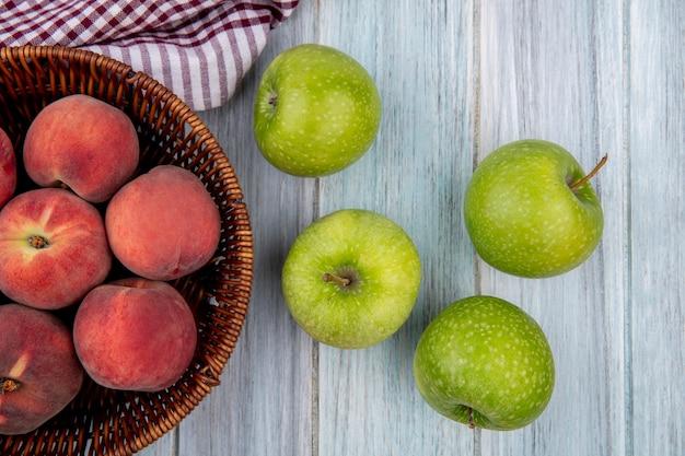 Bovenaanzicht van vers en kleurrijk fruit zoals perziken op emmer op geruit tafelkleed en groene appels geïsoleerd op grijs hout