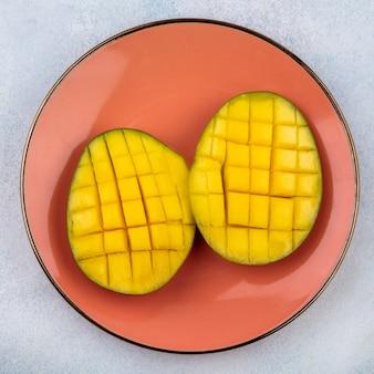 Bovenaanzicht van vers en lekker gesneden mango's op oranje plaat op wit