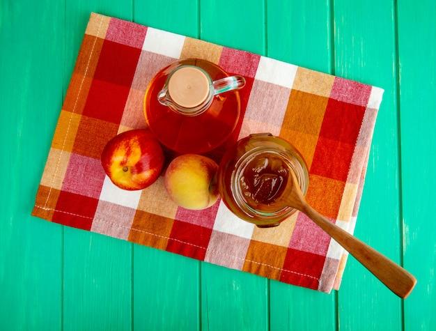 Bovenaanzicht van vers fruit appel met perzik en een fles olijfolie en perzikjam in een glazen pot met een houten lepel op geruite servet op groene houten achtergrond