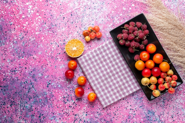 Bovenaanzicht van vers fruit, frambozen en pruimen in zwarte vorm op het roze oppervlak